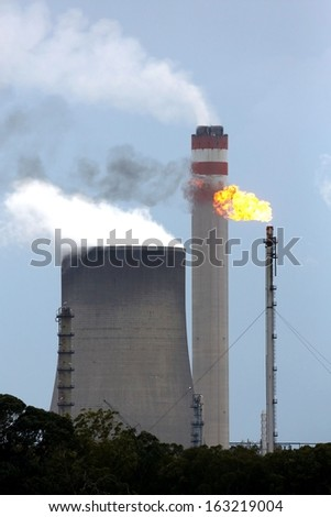 Energy production plant with cooling towers, chimneys and gas flame - stock photo