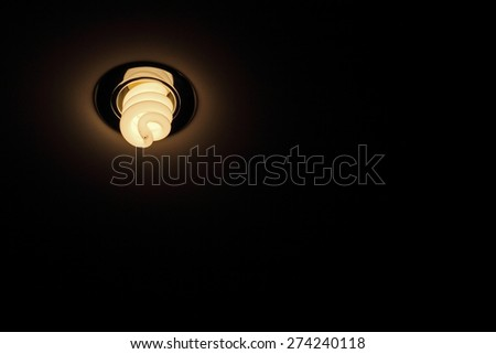 Energy save lamp on ceiling taken closeup on dark background. - stock photo