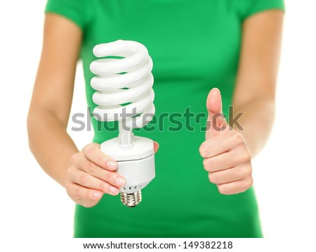 Energy saver light bulb - woman showing big fluorescent light bulb to camera. Green energy, bright idea concept on isolated on white background. - stock photo