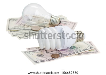 energy saving and normal  lamp bulbs on dollars  isolatd on white - stock photo