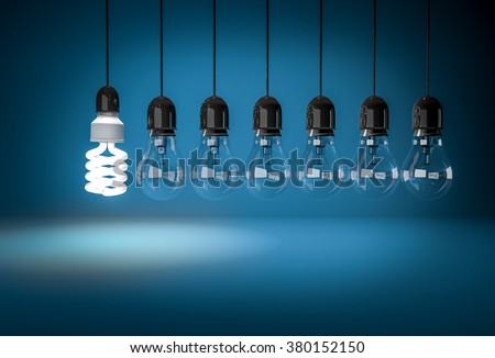 Energy saving bulb lighting incandescent bulbs on wires over blue background. Concept of innovation.