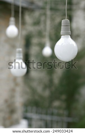 Energy saving bulbs over the wires for electricity - stock photo