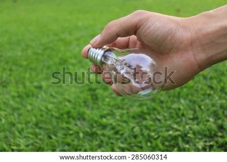 Energy saving concept. Hand holding light bulb on green grass background. - stock photo