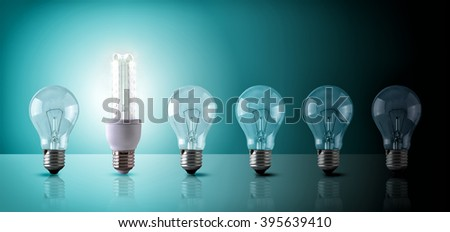 Energy saving concept with light bulbs sequence on a glass table. Led and incandescent bulbs on blue green background. Horizontal composition. Front view - stock photo