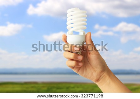 Energy saving concept. Woman hand holding light bulb on abstract nature background. - stock photo
