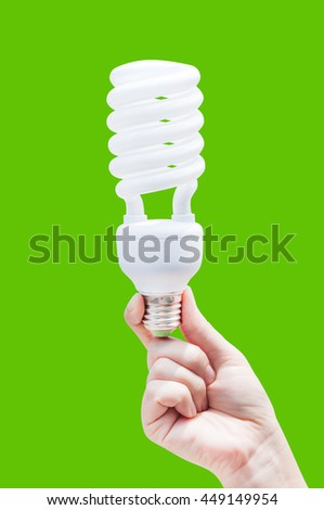 Energy saving concept. Woman hand holding light bulb on green background