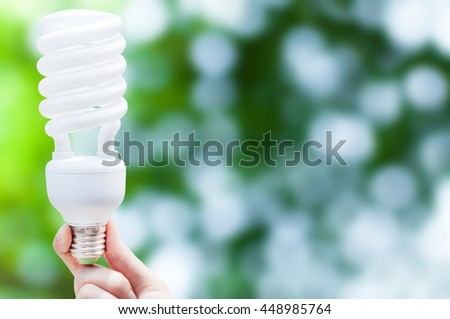Energy saving concept, Woman hand holding light bulb on green nature background,Ideas light bulb in the hand