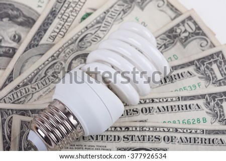 energy saving lamp and dollars closeup