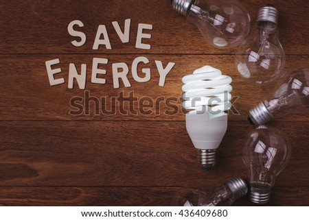 "Energy saving lamp and incandescent lamp and ""save energy"" word on wooden background. Concept for saving energy. Concept for eco-friendly. Concept for global warming. - stock photo"
