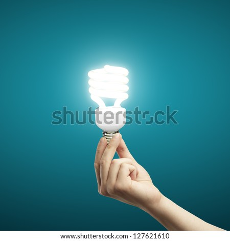 energy saving lamp in hand on blue background