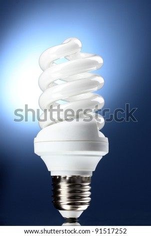 Energy saving lamp on blue background - stock photo