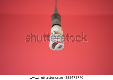 Energy saving light bulb against red wall background - stock photo