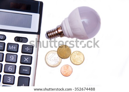 Energy saving light bulb and money on white background seen from above