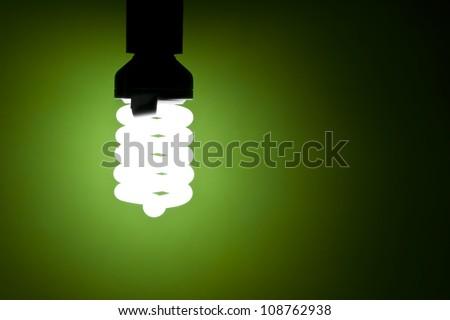 Energy saving light bulb glowing on green background - stock photo