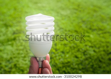 Energy saving light bulb in hand - stock photo