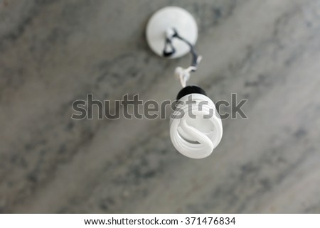 Energy saving light bulb on a ceiling - stock photo