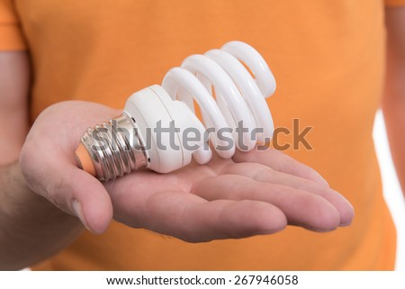 energy saving light bulb on a hand - stock photo