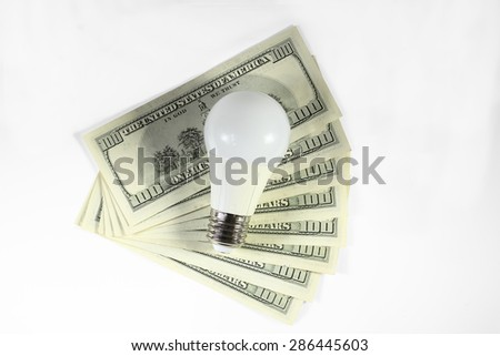 Energy saving - money. Led light bulb on the stack of dollars on a white background