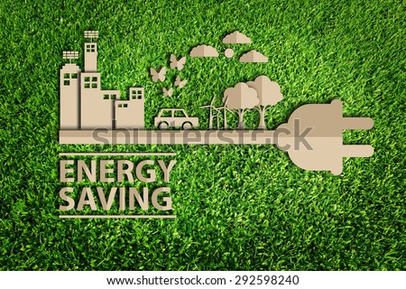 energy saving. Paper cut of Green city concept on green grass. - stock photo