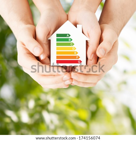 energy saving, real estate and family home concept - closeup of couple hands holding white paper house with energy efficiency rating - stock photo