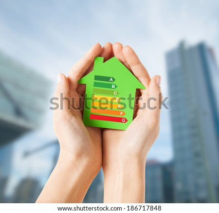energy saving, real estate and family home concept - closeup of female hands holding green paper house with energy efficiency rating - stock photo