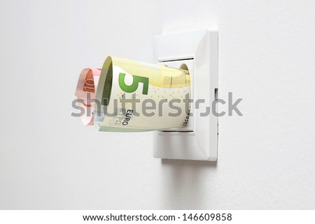 energy savings concept with power socket and money - stock photo