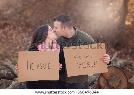 engaged couple kissing and holding cardboard signs on a chilly autumn day - stock photo