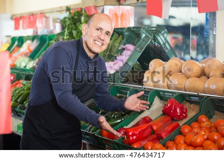 engaged salesman in black apron offering pepper  in vegetable department