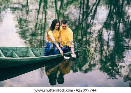 Engaged young couple dreaming about future honeymoon. Young girl and man sitting together in old wooden boat on river. People in love putting paper bouts on water. Romantic boyfriend and girlfriend - stock photo
