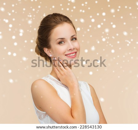 engagement, celebration, wedding and happiness concept - smiling woman in white dress wearing diamond ring over beige background and snow - stock photo