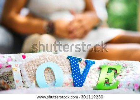 Engagement couple on picnic with letters love in front  - stock photo