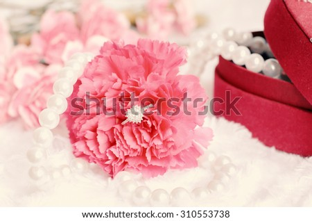 Engagement diamond ring in pink carnation flower with pearl necklace and red jewel box on white fur background - vintage tone - stock photo