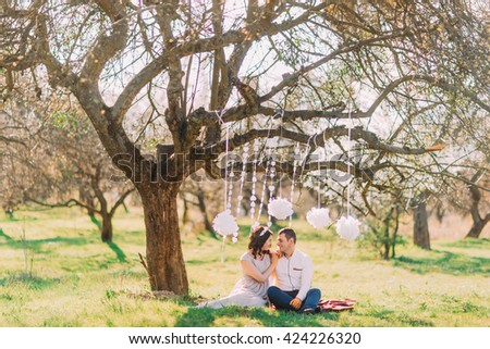 Engagement photo session of beatiful couple in love sitting on plaid. Decorated garden with clouds