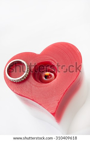 Engagement ring and candle in the heart shape. - stock photo