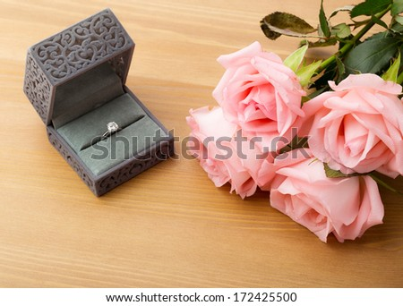 Engagement ring and pink rose  - stock photo
