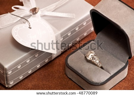 Engagement Ring in box and another gift.