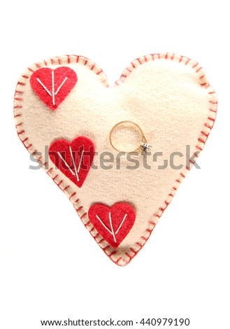Engagement ring on a heart pillow cutout - stock photo