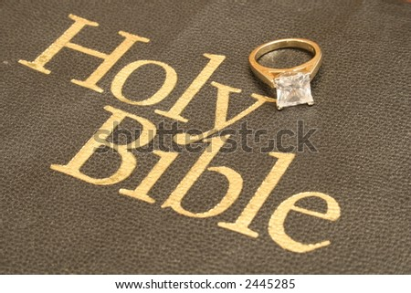 engagement ring on bible upclose - stock photo