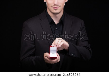 Engagement ring or present in the hands of a man in suit