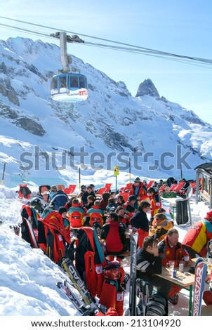 Engelberg, Switzerland - 28 March 2004: Sci tourists drinking and eating at the restaurant on mount Titlis over Engelgerg on the Swiss alps - stock photo