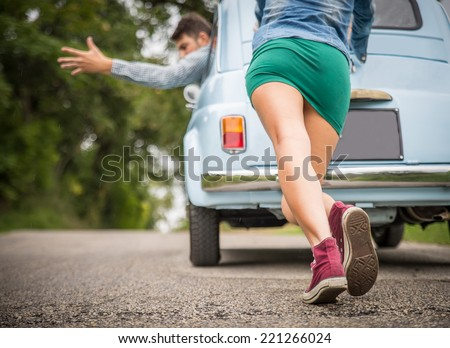 Engine break down.Strong young woman pushing a vintage car while man is emboldening her.Transportation,teamwork,funny concept - stock photo