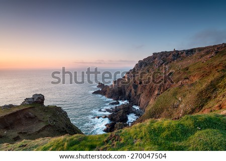 Engine houses perched on the edge of steep rugged cliffs at Botallack near Land's End in Cornwall - stock photo