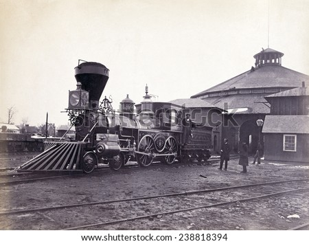 Engine, J.H. Devereux, of the United States Military Railroad with two crew members on board outside the roundhouse at the Alexandria station. Albumen print, photo by Andrew J. Russell, ca. 1860s - stock photo
