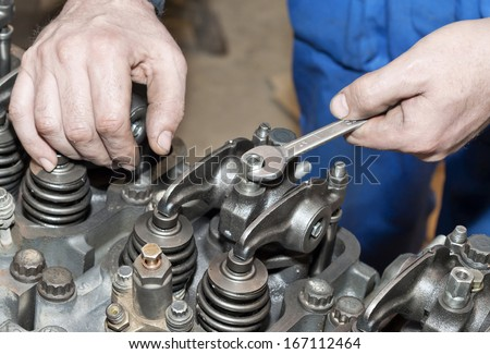 Engine repair with spanner in hand, close up.