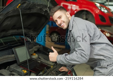 Engine test approved. Smiling mechanic testing an engine with computer and showing thumb up