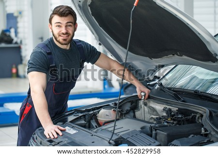Engine tunage. Professional car mechanic smiling to the camera while working at his repair shop - stock photo