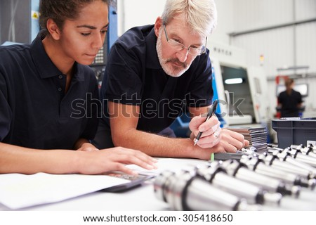 Engineer And Apprentice Planning CNC Machinery Project - stock photo