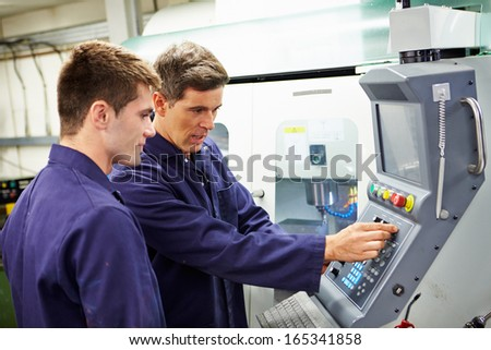 Engineer And Apprentice Using Automated Milling Machine - stock photo