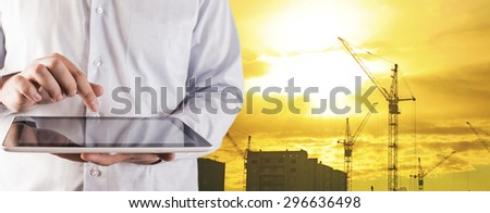 Engineer and architect hold digital tablet computer on sunset sky with clouds and sun background No face Unrecognizable person New highrise apartment buildings and construction cranes Silhouette Crane - stock photo