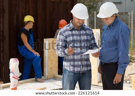 Engineer and architect wearing hardhats standing discussing paperwork on a construction site with builders working behind them - stock photo